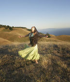 Passionate woman dancing on hillside — Stock Photo