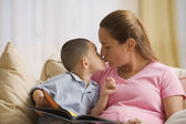 Mother and son kissing as they read together — Stock Photo