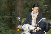 Portrait of woman riding scooter — Stock Photo