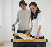 Hispanic couple measuring wood — Stock Photo