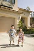 Young Asian brother and sister holding hands in driveway — Stock Photo