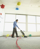 Man vacuuming after office party — Stock Photo