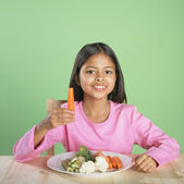 Portrait of Hispanic girl with plate of vegetables — Stock Photo