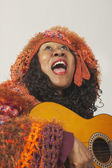 African woman singing and holding guitar — Stock Photo