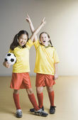 Two girls cheering in soccer outfits — Stock Photo