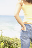 Midsection of woman looking at ocean — Stock Photo