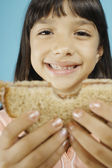 Young girl holding sandwich — Stock Photo