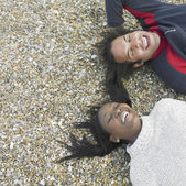 Young couple smiling and laying on beach — Stock Photo