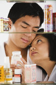 Portrait of Asian couple through medicine cabinet — Stock Photo