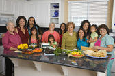Large Hispanic family in kitchen with food — Stockfoto