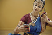 Indian woman in traditional dress using a electronic organizer and a cell phone — Stock Photo