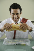 Businessman eating big sandwich — Stock Photo