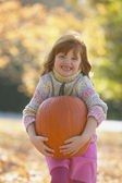 Young girl smiling and holding pumpkin outdoors — Stok fotoğraf