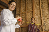 Hispanic couple using tape measure in construction site — Stock Photo