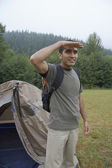 Indian man shading eyes at campsite — Stock Photo