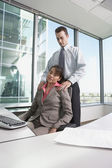 Hispanic businessman giving Hispanic businesswoman a shoulder massage in her cubicle — Stock Photo