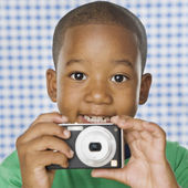 Young African boy holding camera — Stock Photo