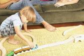 Jovem rapaz jogando com trens no chão da sala — Foto Stock