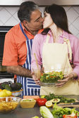 Middle-aged Hispanic couple kissing in kitchen — Stock Photo