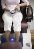 Woman adjusting seat in pedicure chair — Stock Photo