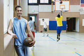 Man holding basketball with team warming up behind him — Stock Photo