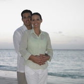 Par poserar på stranden — Stockfoto