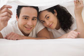 Hispanic couple lying under the sheet on the bed and smiling — Stock Photo