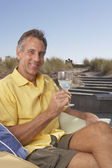 Portrait of man sitting holding wine glass at beach — Stock Photo