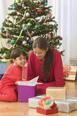 Brother and sister opening Christmas gift in front of tree — Stock Photo