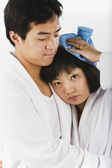 Asian man hugging sick girlfriend — Stock Photo