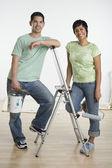 Portrait of Hispanic couple holding painting supplies — Stock Photo
