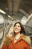 Woman using cell phone at train station — Stock Photo