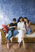 Hispanic mother and children relaxing on sofa — Stock Photo