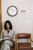 读一本杂志在等候室的年轻女子 — 图库照片