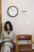 Young woman reading a magazine in waiting room — Stock Photo