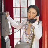 Asian woman using public telephone box in London — Stock Photo