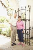 Senior Hispanic couple standing next to iron gate — Stock Photo