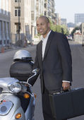 Businessman with briefcase next to scooter — Stock Photo