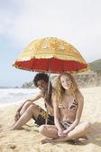 Young couple under sun umbrella on beach — Stock Photo