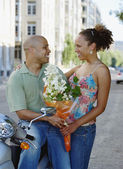 Couple looking at each other with bouquet of flowers — Stock Photo