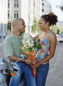 пара, глядя друг на друга с букетом цветов — Стоковое фото