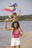 Hispânica mãe e filha voando kite na praia — Fotografia Stock