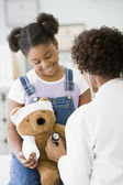 African American female doctor examining girl's teddy bear — Stock Photo