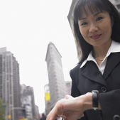 Businesswoman smiling with cityscape behind her — Stock Photo
