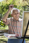 Senior man painting with easel outdoors — Stock Photo