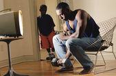 アフリカ人の息子を監視しながら、ダンベルを持ち上げる — ストック写真