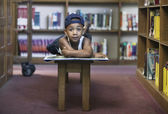 Portrait of boy reading book at library — Stock Photo