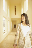 Hispanic woman walking down sunlit hallway — Stock Photo