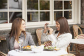 Woman having her photograph taken by other woman at lunch — Stock Photo