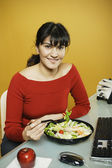 Businesswoman eating salad at desk — Stock Photo
